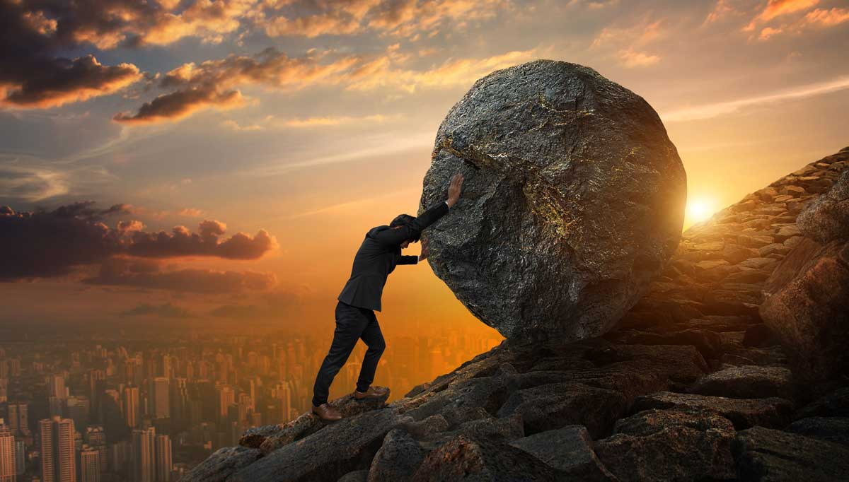 person pushing boulder up a mountain with help of a business coach