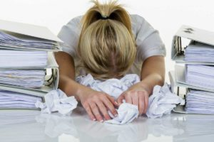 girl with head on desk piled with papers from poor delegating